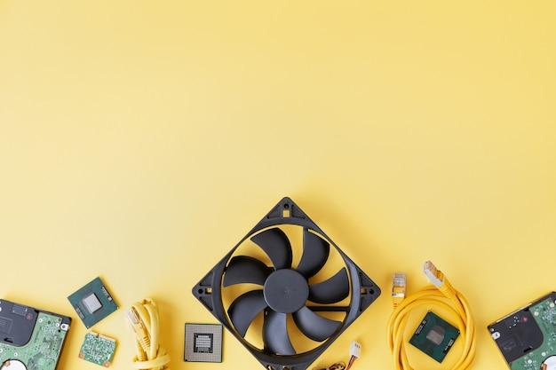 Ram so-dimm, cpu, ventilator, usb, wi-fi-module, harde schijven, patchkabel op de gele achtergrond plat leggen