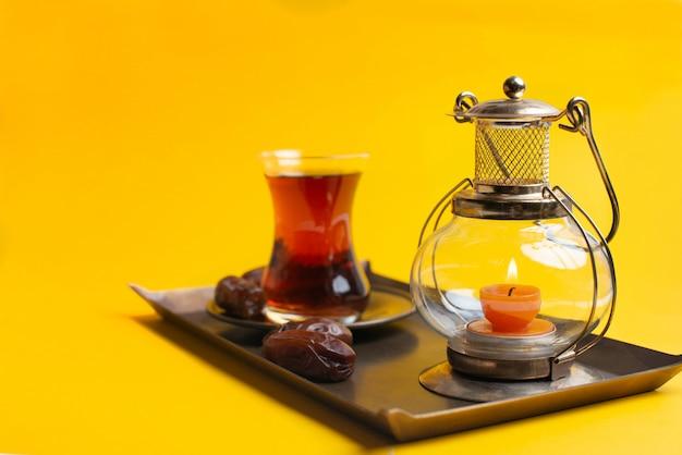 Ramadan kareem feestelijk, close up van dadels op bord met oosterse kaarslamp en kopje zwarte thee