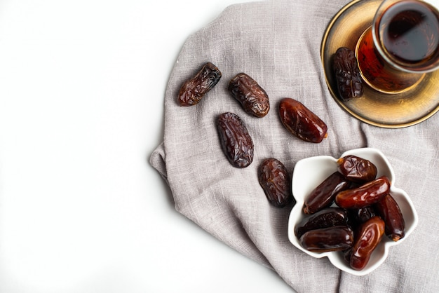 Ramadan kareem feestelijk, close-up van dadels op kom en kopje zwarte thee