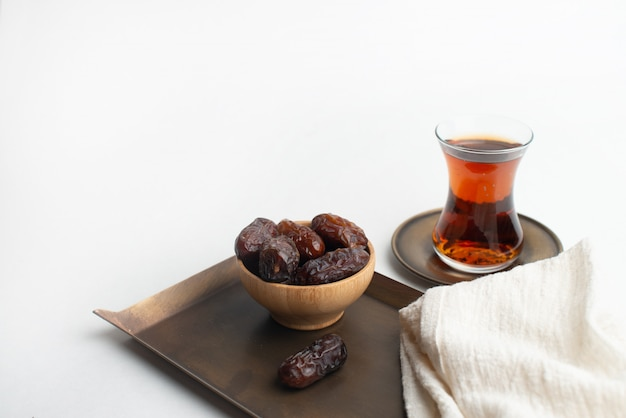 Ramadan kareem festival, data op houten schaal met kopje zwarte thee en rozenkrans