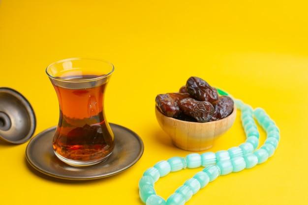 Ramadan kareem festival, datums op houten kom met kopje zwarte thee en rozenkrans op gele achtergrond