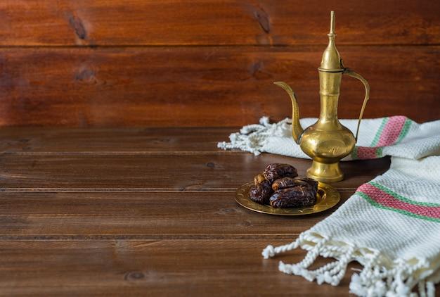 Ramadan voedselbereiding, theepot met datums, iftar voedsel op houten achtergrond met kopie ruimte