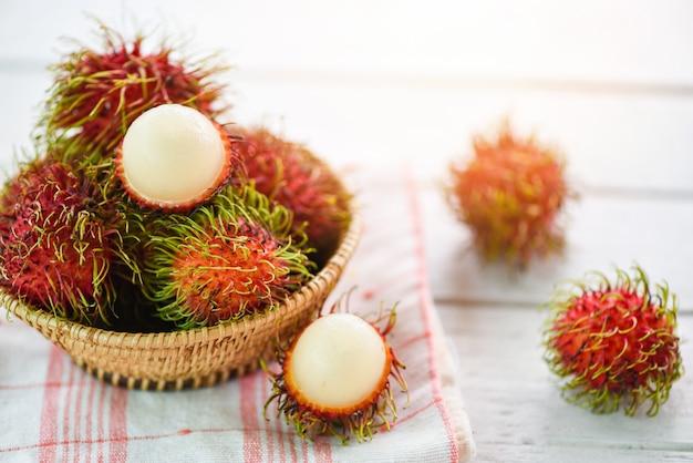 Rambutan geschild in een mand op tafel - vers rambutan zomerfruit uit de tuin in thailand