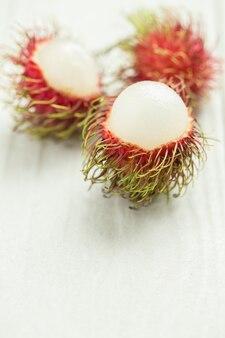 Rambutan op witte houten lijst, rode ramboetan gepeld