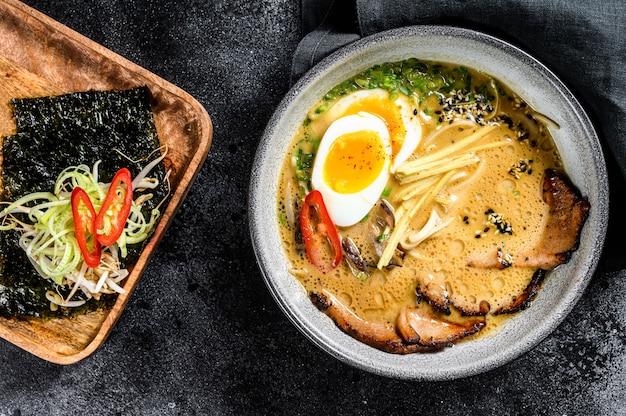 Ramen aziatische noedelsoep met rundertongvlees, champignons en ajitama gepekeld ei. zwarte achtergrond. bovenaanzicht