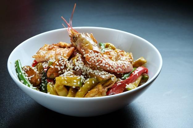 Ramen tarwenoedels met mosselen, garnalen en groenten gebakken in een wok in een witte kom op zwart. selectieve aandacht. detailopname. lekker straatvoedsel. zeevruchten