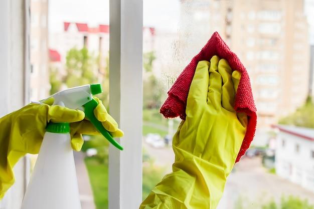 Ramen wassen. vrouw in gele rubberen handschoenen veegt het glas af.