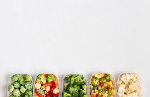 Rand van bevroren groenten in plastic bakjes op een witte achtergrond. diepvries voedsel. kopieer ruimte, bovenaanzicht, plat leggen.