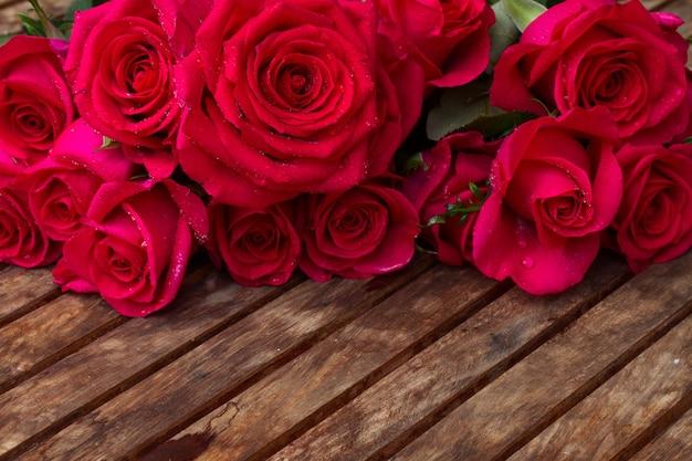 Rand van donker roze rozen op houten tafel