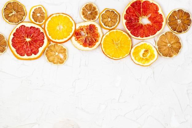 Rand van gedroogde plakjes van verschillende citrusvruchten op witte muur. oranje citroen grapefruit met copyspace