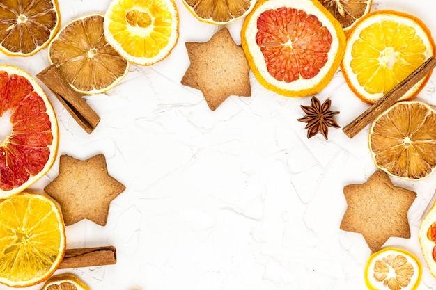 Rand van gedroogde plakjes van verschillende citrusvruchten peperkoek en kruiden op witte achtergrond met copyspace. kerst frame