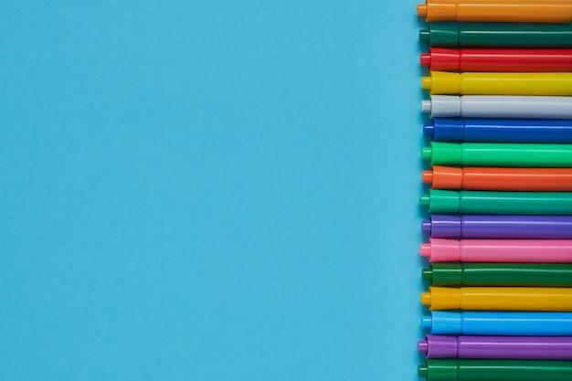Rand van gekleurde viltstiften op blauwe achtergrond met copyspace