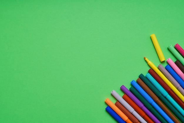 Rand van gekleurde viltstiften op heldergroene achtergrond met copyspace. bovenaanzicht