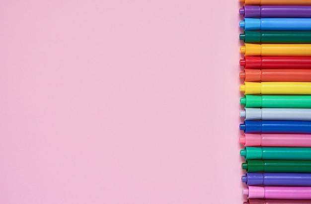 Rand van gekleurde viltstiften op roze achtergrond met copyspace
