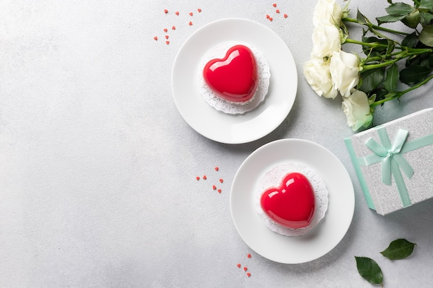 Rand van hartvorm mousse taarten, roze bloemen, geschenkdoos