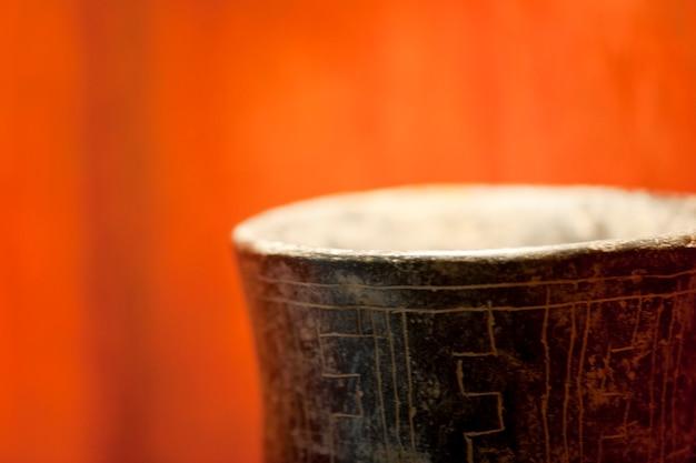 Rand van ingeschreven bruine buitenkant en witte binnenlandse vaas tegen trillende oranje achtergrond