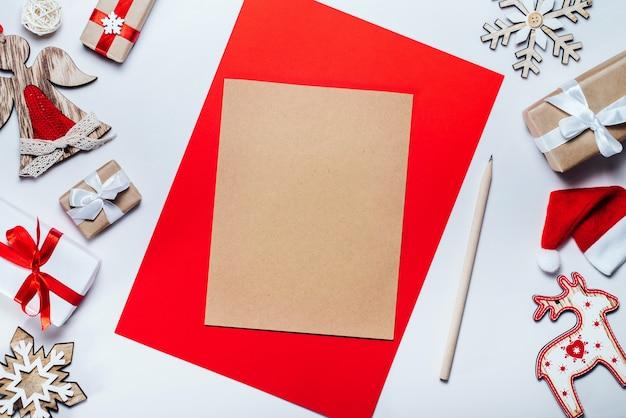 Rand van kerstversiering en geschenkdozen met blanco stuk ambachtelijk papier om vakantiewensen te schrijven. bovenaanzicht, plat gelegd.