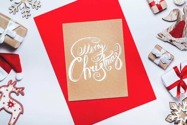 Rand van nieuwjaar versieringen en geschenken op witte achtergrond met merry christmas wensen geschreven met kalligrafische lettertype op ambachtelijke papier stuk
