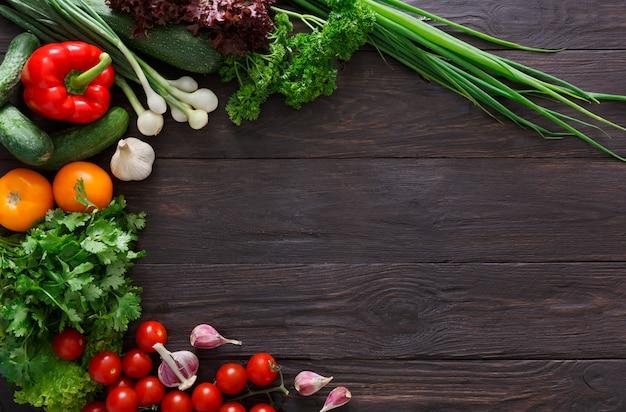 Rand van verse groenten op houten achtergrond met kopie ruimte