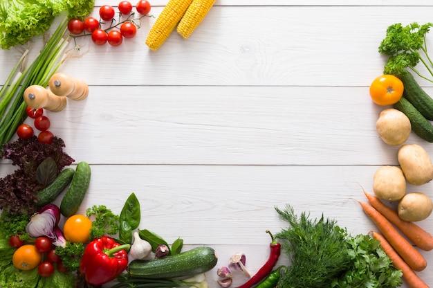 Rand van verse groenten op wit hout met kopie ruimte