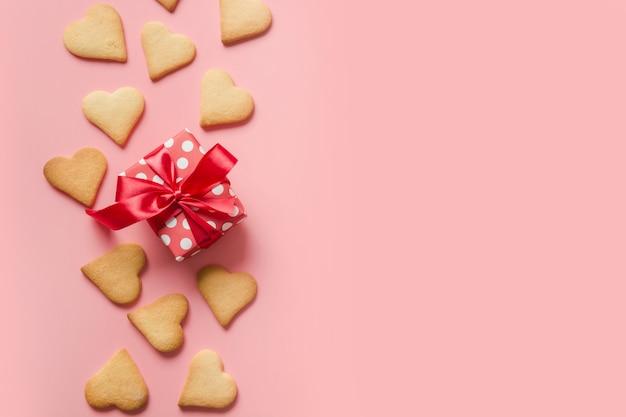 Rand van zelfgemaakte hartvormige koekjes en cadeau op roze.