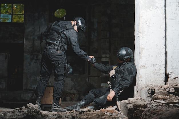 Ranger in zwart uniform helpt zijn kameraad