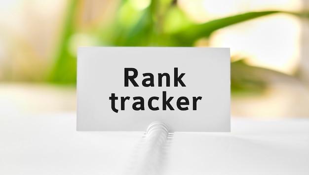 Rank tracker - bedrijfsconceptentekst op een wit notitieboekje en groene bloemen