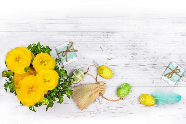 Ranonkel boterbloemen, wenskaarten, beschilderde paaseieren, veren, canvas tas met geschenken