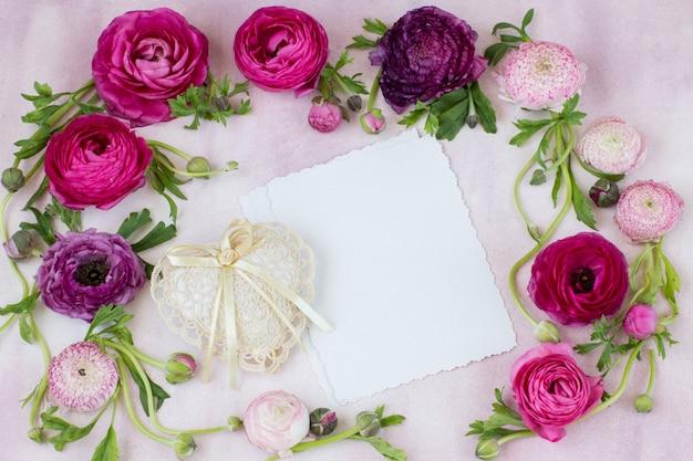 Ranunculus bloemen, een stuk papier en een hart van kant