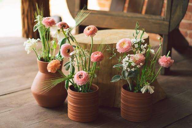 Ranunculus bloemen in aarden potten op het terras mooie bloemen in een vaas