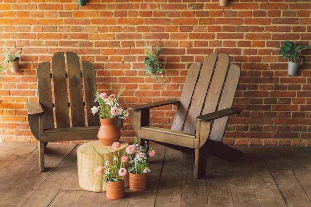 Ranunculus bloemen in aarden potten op het terras twee houten stoelen op het terras met een mooie bri...