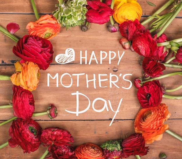 Ranunkulyus boeket van rode bloemen op een houten achtergrond. gelukkig moederdag concept