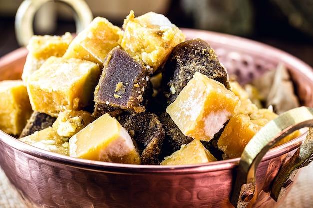 Rapadura-snoep in stukjes in een koperen pot, snoep gemaakt van suikerriet of melasse van suikerriet