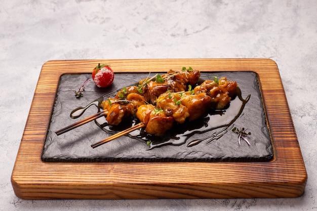 Rapana shish kebab met teriyakisaus en romidor, op zwarte leisteen, op een houten bord, op een witte achtergrond