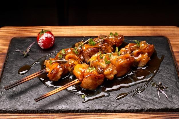 Rapana shish kebab met teriyakisaus en romidor, op zwarte leisteen, op een houten bord