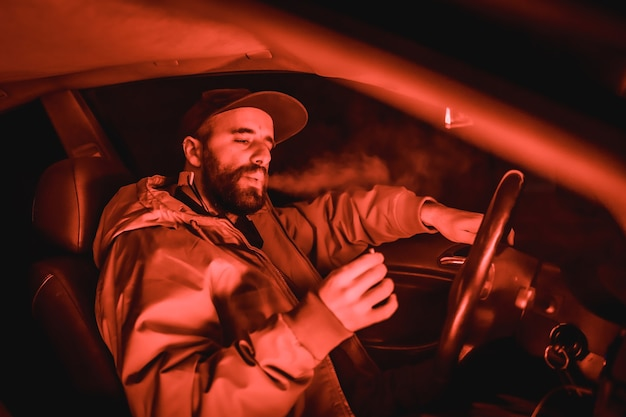 Rapper man in een pet in een auto die 's nachts rookt in een garage verlicht met een rood licht in de winter, sportwagen