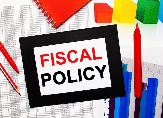Rapporten en kleurenkaarten liggen op tafel. er zijn ook rode pennen, potlood en papier in een zwarte lijst met de woorden fiscal policy. uitzicht van boven