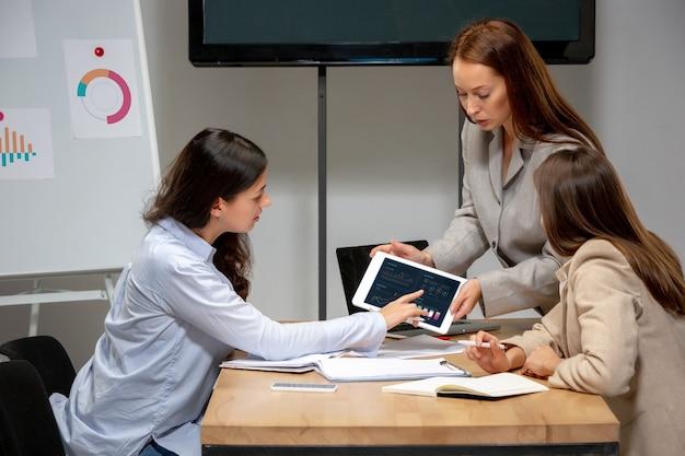 Rapporten. jonge vrouwen praten, werken met apparaten met collega's op kantoor of in de woonkamer. webshop, onderwijs tijdens isolatie, quarantaine. werk, financiën, tech concept.