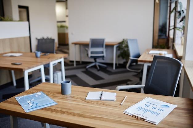 Rapporten met verkoopgegevens geopende planner en kopje koffie op tafel van ondernemer in leeg kantoor