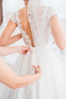 Rasp de keuze uit prachtige modejurken die hangen aan rekken in de garderobe van de vrouw. een grote variëteit aan fonkelende kleding.