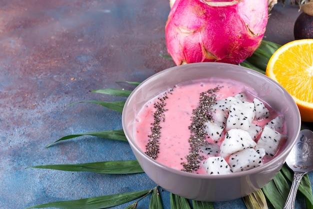 Raspberries rode of roze die smoothiekommen met verse pitaya en chiazaden worden bedekt op palmblad op steenachtergrond, exemplaarruimte