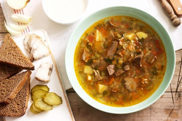 Rassolnik, traditionele russische soep, geserveerd met verschillende snacks en wodka.