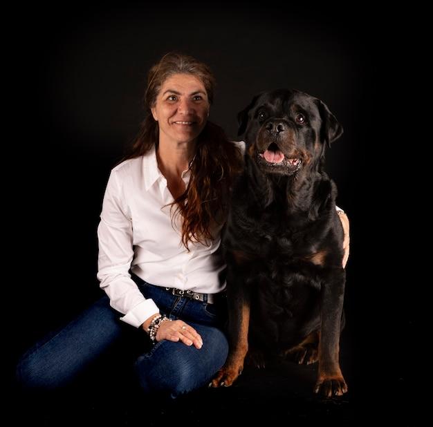 Raszuivere rottweiler en vrouw voor zwarte oppervlakte