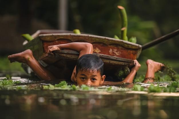 Ratchaburi, thailand - april 9,2019: jongen die in cannal dichtbij de drijvende markt van damnoen saduak zwemmen