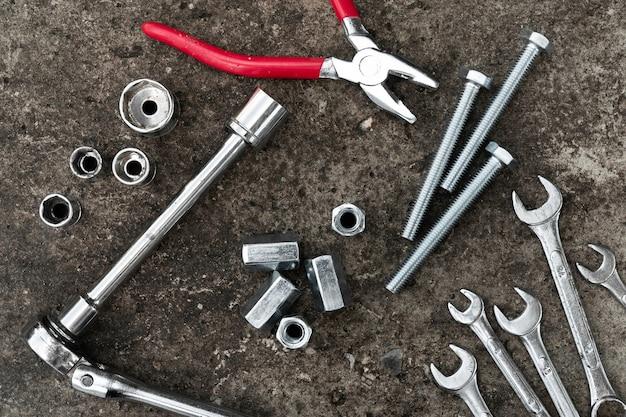 Ratelde moersleutel, tang, bouten en moersleutels op concrete achtergrond.