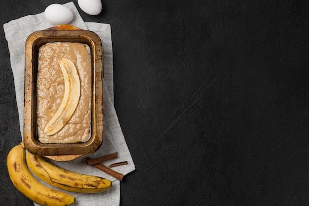 Rauw bananenbrooddeeg in rechthoekige ovenschaal met ingrediënten op zwarte achtergrond