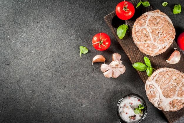 Rauw biologisch vlees. kipkoteletten voor hamburgers, met een rooster van varkensvlees, voor grillen of braden. met kruiden, basilicum, tomaten, op een grijze stenen tafel op een snijplank. bovenaanzicht