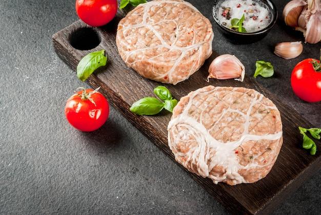 Rauw biologisch vlees. kipkoteletten voor hamburgers, met een rooster van varkensvlees, voor grillen of braden. met kruiden, basilicum, tomaten, op een grijze stenen tafel op een snijplank. copyspace