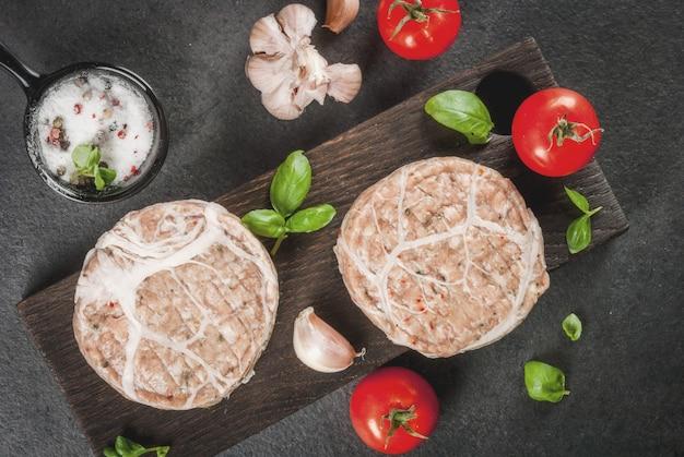 Rauw biologisch vlees. kipkoteletten voor hamburgers, met een rooster van varkensvlees, voor grillen of braden. met kruiden, basilicum, tomaten, op een grijze stenen tafel op een snijplank. kopieer ruimte bovenaanzicht