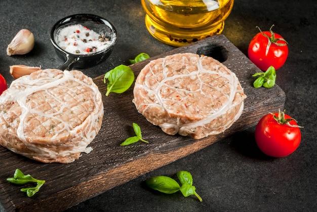 Rauw biologisch vlees. kipkoteletten voor hamburgers, met een rooster van varkensvlees, voor grillen of braden. met kruiden, basilicum, tomaten, op een grijze stenen tafel op een snijplank.